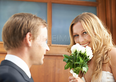 Buy stock photo A beautiful woman holding a bunch of white flowers in her hand with her boyfriend standing in front of her