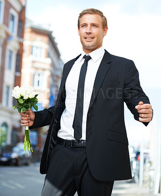 Buy stock photo A handsome man standing in the street with white roses in his hand and looking into the distance