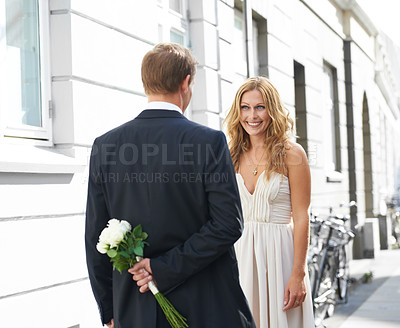 Buy stock photo A beautiful woman smiles at her boyfriend holding a bunch of white roses behind his back