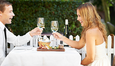 Buy stock photo A beautiful couple hold wineglasses and toast at restaurant