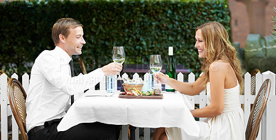 Buy stock photo A beautiful couple hold wineglasses and toast at a restaurant
