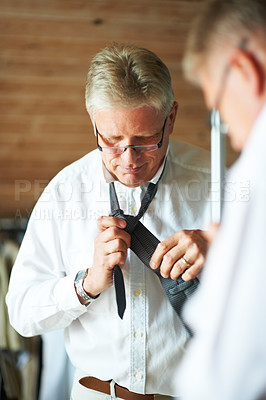 Buy stock photo Cropped shot of a senior man getting ready for work in the morning