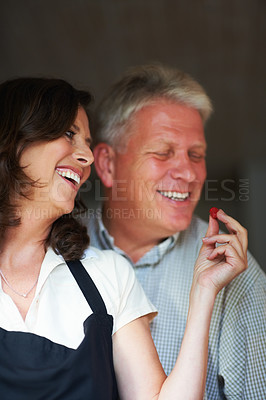 Buy stock photo Cropped shot of a senior woman feeding her husband a raspberry in the kitchen