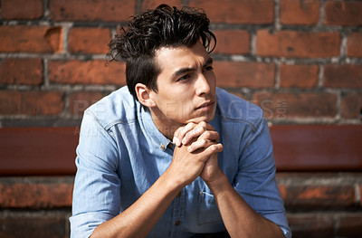 Buy stock photo A handsome young man looking away thoughtfully with his hands clasped