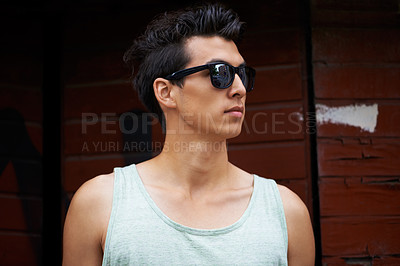 Buy stock photo A trendy young man looking away while wearing shades