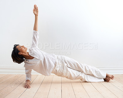 Buy stock photo A fit young woman performing the side plank pose during her yoga routine