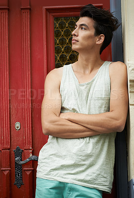 Buy stock photo A thoughtful young man leaning against the doorway and looking away