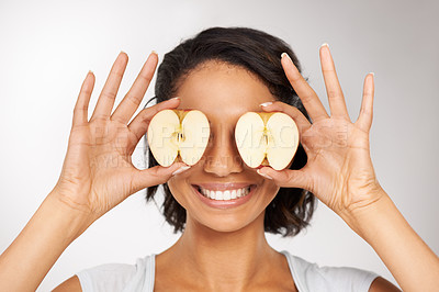 Buy stock photo Shot of a young woman covering her eyes with two apple halves
