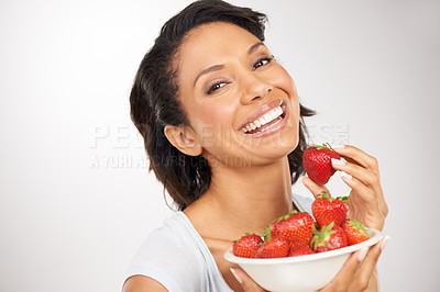Buy stock photo Portrait of a young woman enjoying a bowl of strawberries