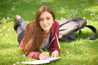 Buy stock photo A lovely young woman writing in her notepad while lying on the grass in a field