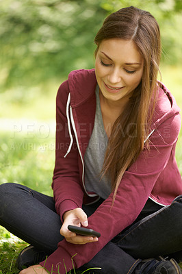 Buy stock photo A pretty young woman texting on her phone while sitting in a green field