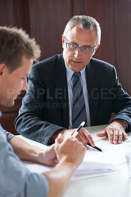 Buy stock photo Shot of two colleagues discussing paperwork together