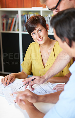 Buy stock photo Shot of a young couple meeting with their financial advisor