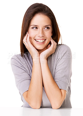 Buy stock photo Studio shot of a beautiful young woman sitting with her chin rested on her hands against a white background