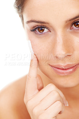 Buy stock photo Studio shot of a beautiful young woman applying a skincare product to her face