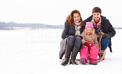 Buy stock photo Two adolescents and a child sitting on a snow sled outdoors on a crisp winter's day
