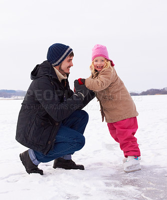 Buy stock photo Older brother teaching his daughter how to skate on a frozen natural lake