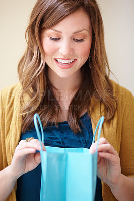 Buy stock photo Cropped shot of an attractive young woman looking happily into a shopping bag