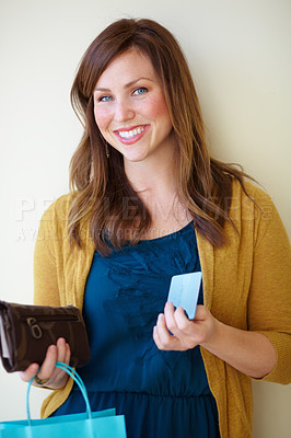 Buy stock photo A smiling young woman holding her shopping bag, purse and handbag