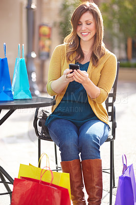 Buy stock photo Shot of an attractive young woman texting a friend about all the bargains she found