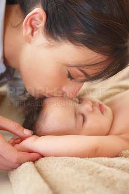 Buy stock photo Close up shot of a mother tenderly kissing her slumbering baby