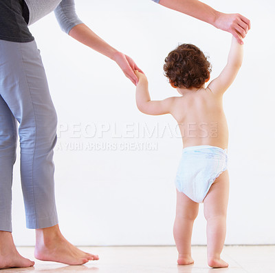 Buy stock photo Rearview studio shot of a mother helping her baby take his first steps