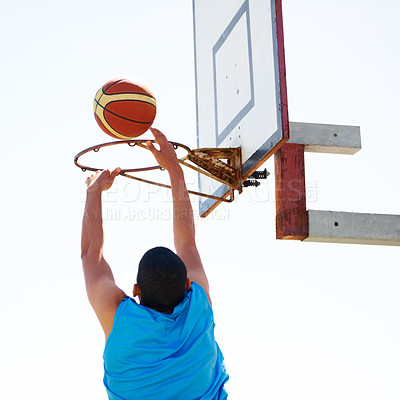 Buy stock photo A young basketball player scoring a slam dunk