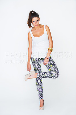 Buy stock photo Full length studio shot of an attractive young woman with her leg raised posing for the camera