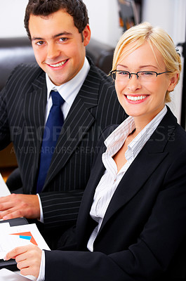 Buy stock photo Portrait of an adorable business executive in an office with a male colleague in the background.