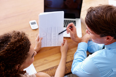 Buy stock photo A businessman and businesswoman discuss a spreadsheet