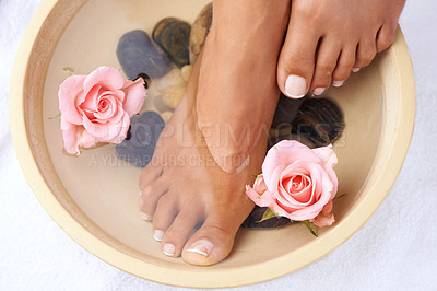 Buy stock photo Shot of a beautiful woman's feet soaking in a bowl filled with flowers and water