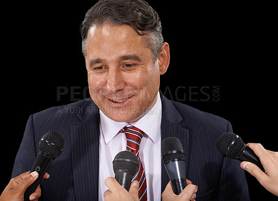 Buy stock photo A mature man in a suit doing a press conference on a black background