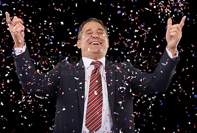 Buy stock photo A man in a suit with his arms raised in victory and ticker tape falling around him