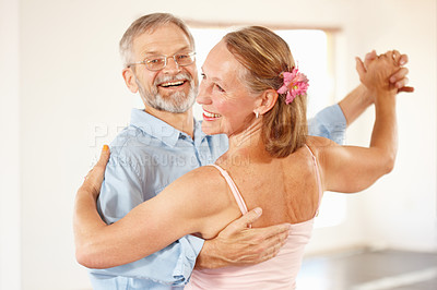 Buy stock photo Shot of a  mature couple happily waltzing together indoors