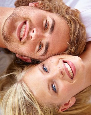 Buy stock photo Portrait of a young couple lying in bed with their heads together
