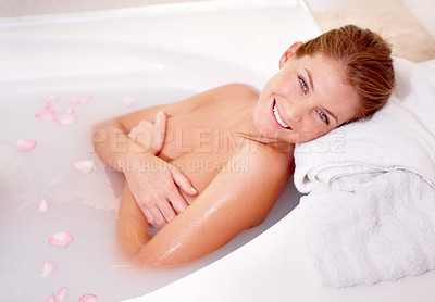 Buy stock photo A gorgeous young woman lying in a luxurious bath of rose petals