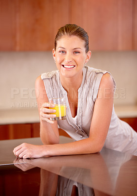 Buy stock photo A gorgeous young woman enjoying a glass of orange juice in her kitchen