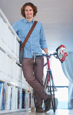 Buy stock photo Shot of a young businessman arriving at work with his bicycle