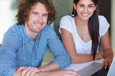 Buy stock photo Cropped shot of two young business colleagues working on a laptop