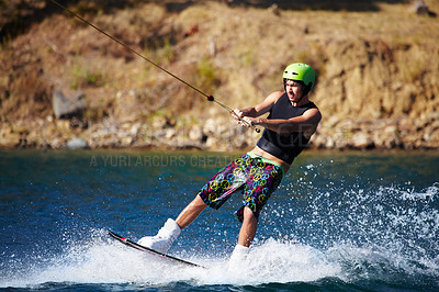 Buy stock photo A young man wearing a helmet and lifejacket wakeboarding on a lake