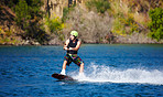 A young man wearing a helmut and lifejacket wakeboarding on a lake