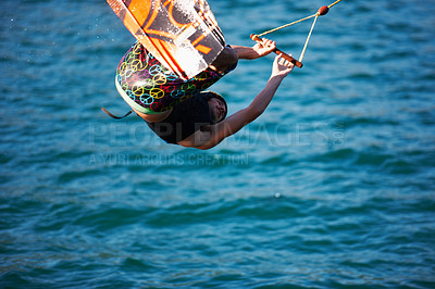 Buy stock photo A young man wearing a helmut and lifejacket wakeboarding on a lake