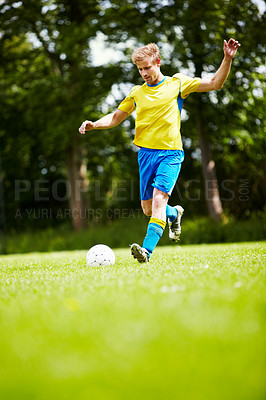 Buy stock photo Shot of a soccer player running up to kick the ball with gusto