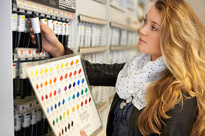 Buy stock photo Shot of a young female artist comparing tubes of paint to a colour chart in an art store