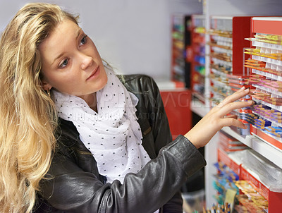 Buy stock photo Shot of a young female artist looking at a variety of pencils or chalk in an art store
