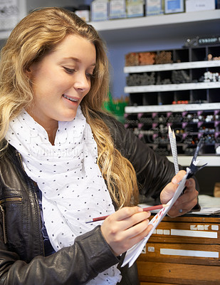 Buy stock photo A young woman in an art supply store testing out some of the pens