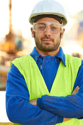 Buy stock photo A stern construction working wearing protective glasses and crossing his arms