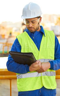 Buy stock photo An engineer overseeing the construction of his blueprints
