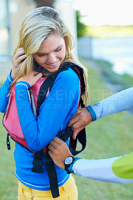 Buy stock photo Cropped shot of an attractive young woman getting some  assistance with her life jacket