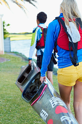 Buy stock photo A cropped shot of two young people carrying a kayak